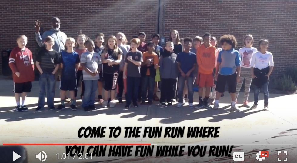 Screen shot of Family Fun Run Video - Teacher With Students in front of school
