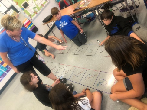 Amy Lamb, 5th Grade Coleridge Teacher, letting students write on the floor to solve problems