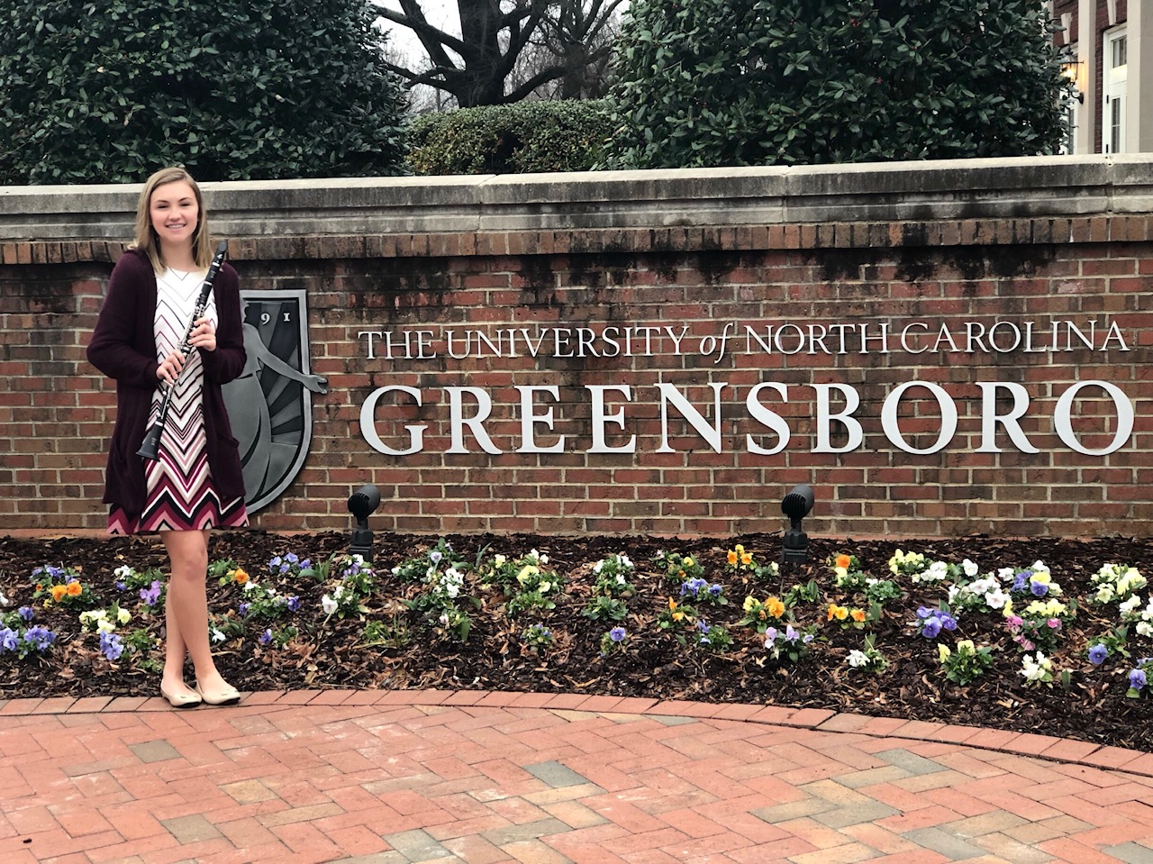Student holding musical instrument in front of the UNC-Greensboro sign.
