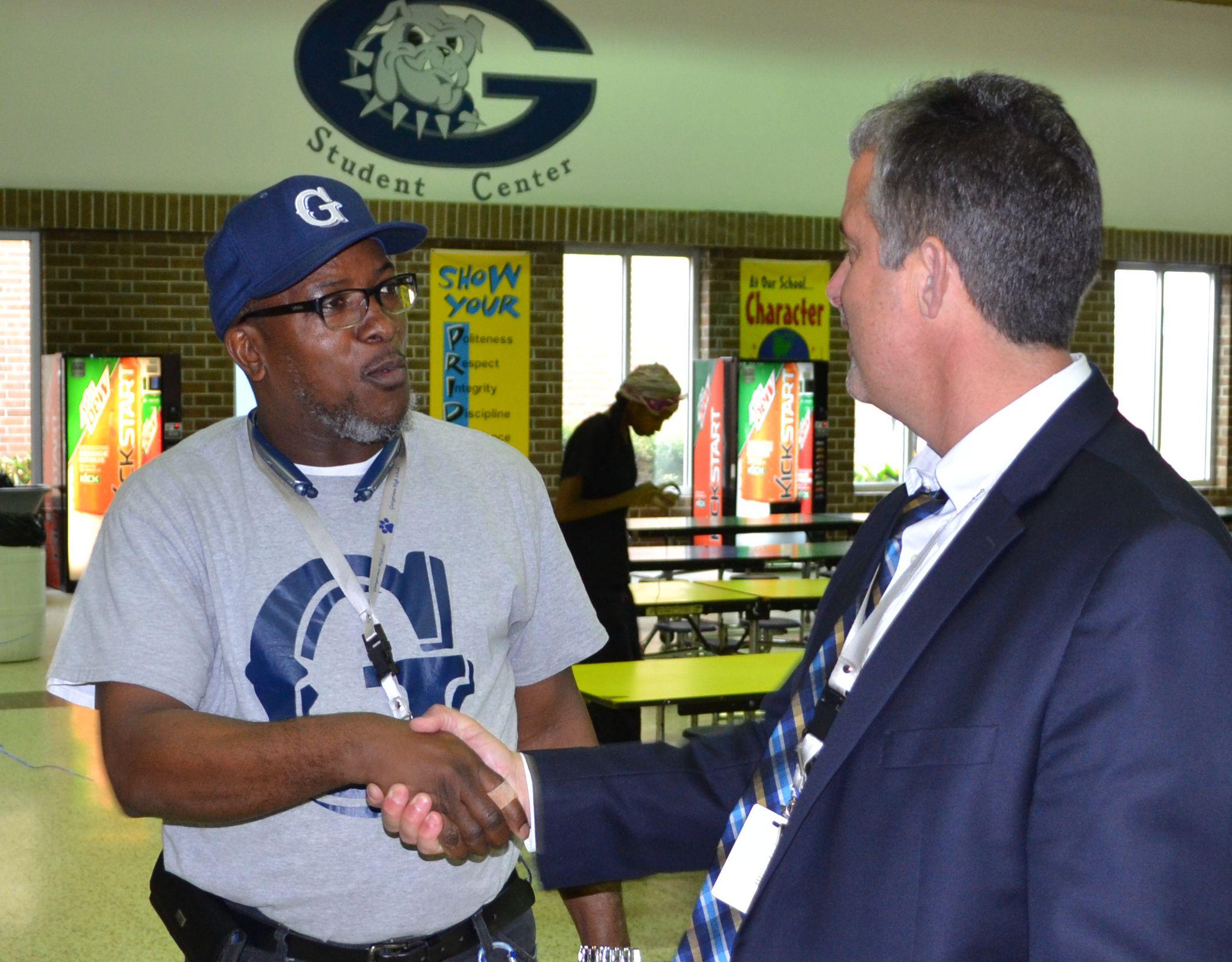 Rev. Jackson congratulated by Principal Craig Evans