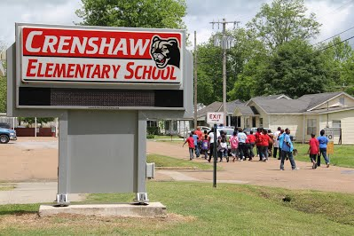 Picture of the outside of Crenshaw Elementary with school sign and students.