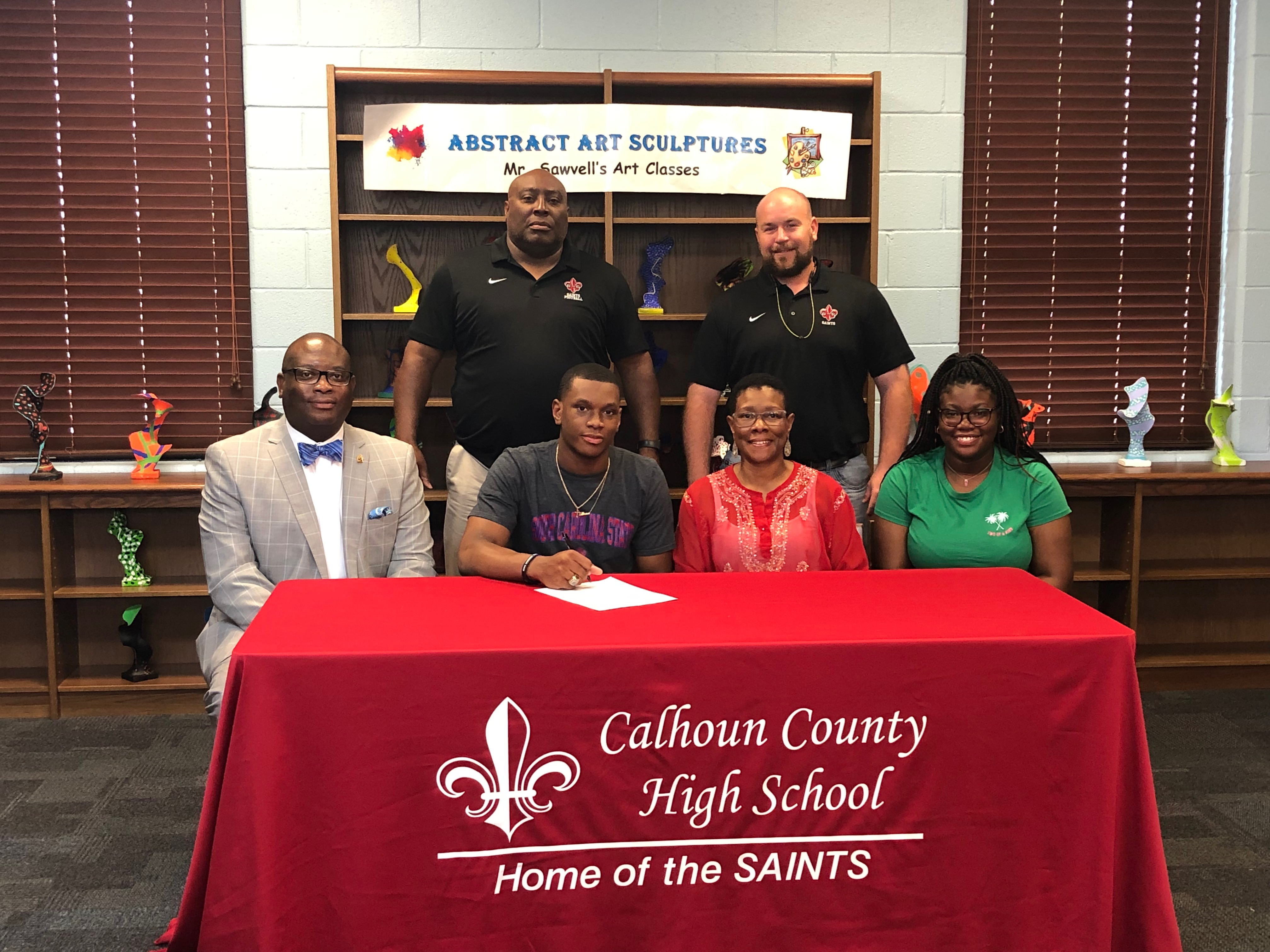 Tullock is pictured with Calhoun County High School Head Football Coach Wayne Farmer, CCHS Athletic Director Justin Farmer, and family members