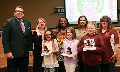 Christmas card winners with superintendent, assist superintendent, principals, and board member
