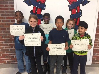 Children holding awards for being STAR athletes of the week.