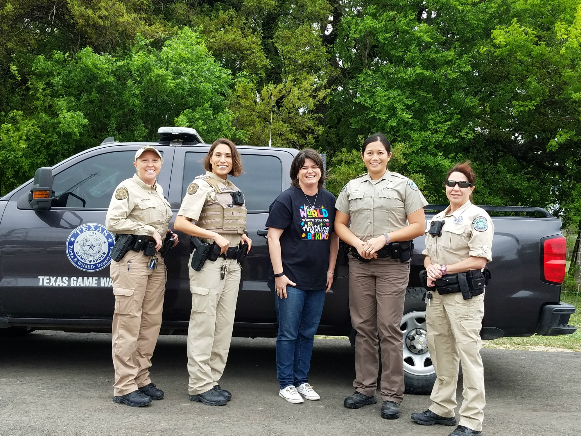 Game Wardens pose with Mrs. Santos