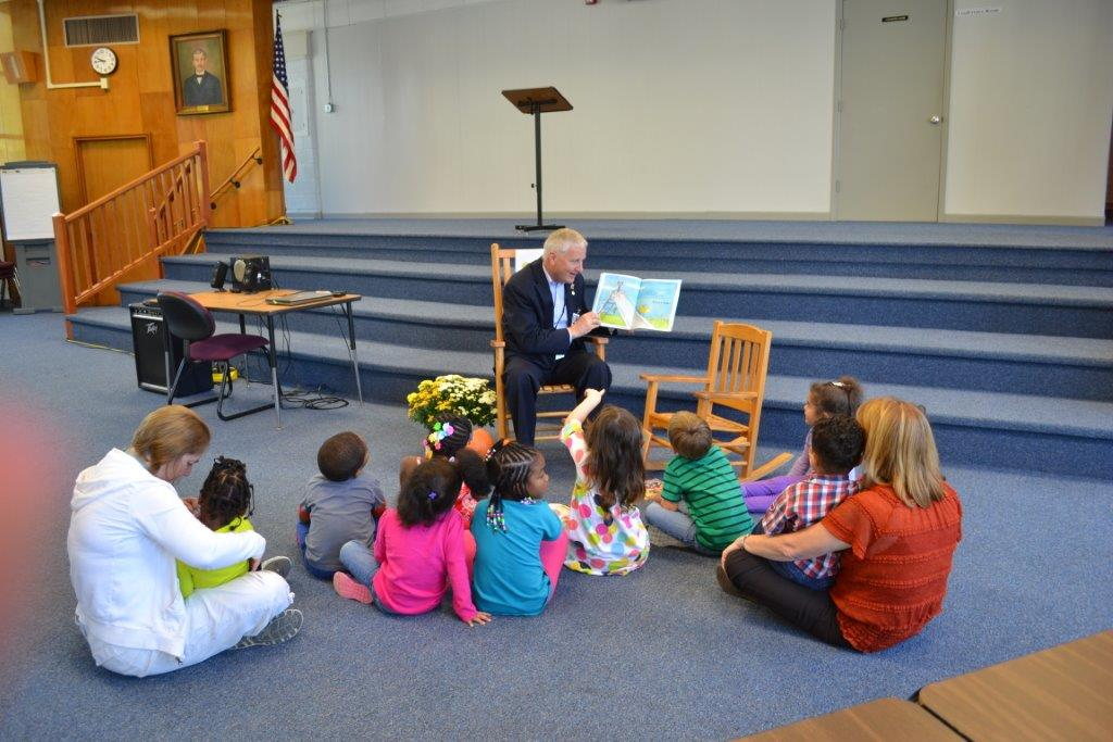 school board member reading to students