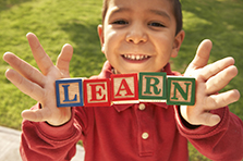 decorative image of boy holding blocks that spell LEARN