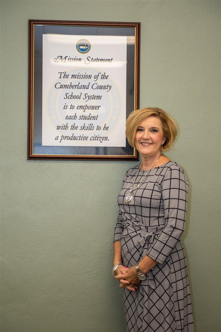 Mrs Graham standing beside the mission statement